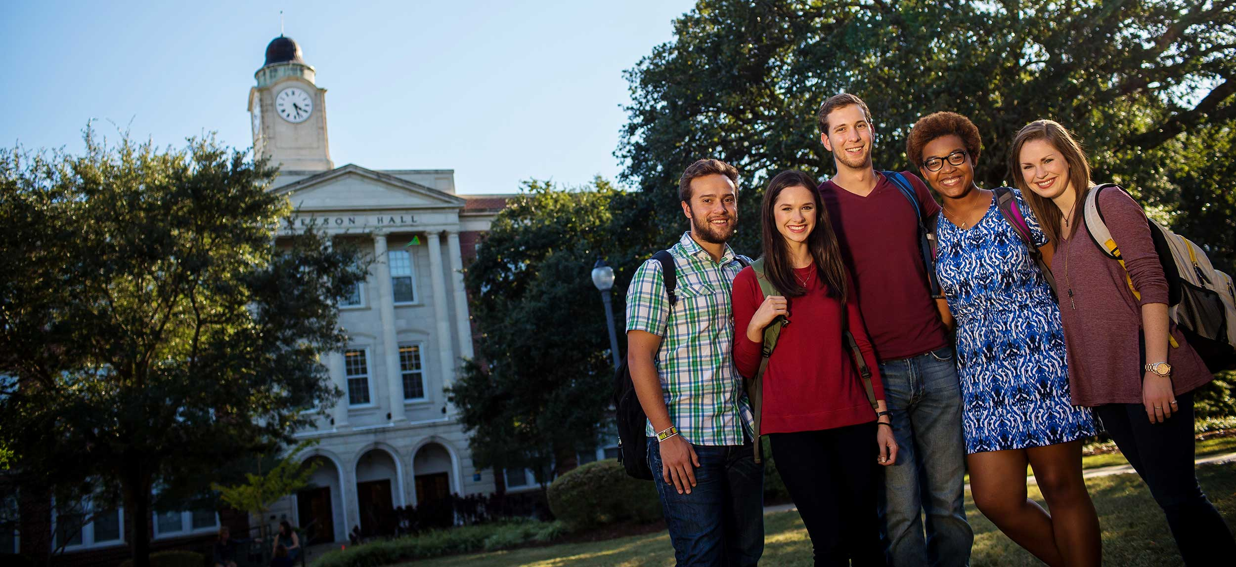 Five students posing for a photo on the Quad in front of Nelson Hall on Mississippi College's campus.