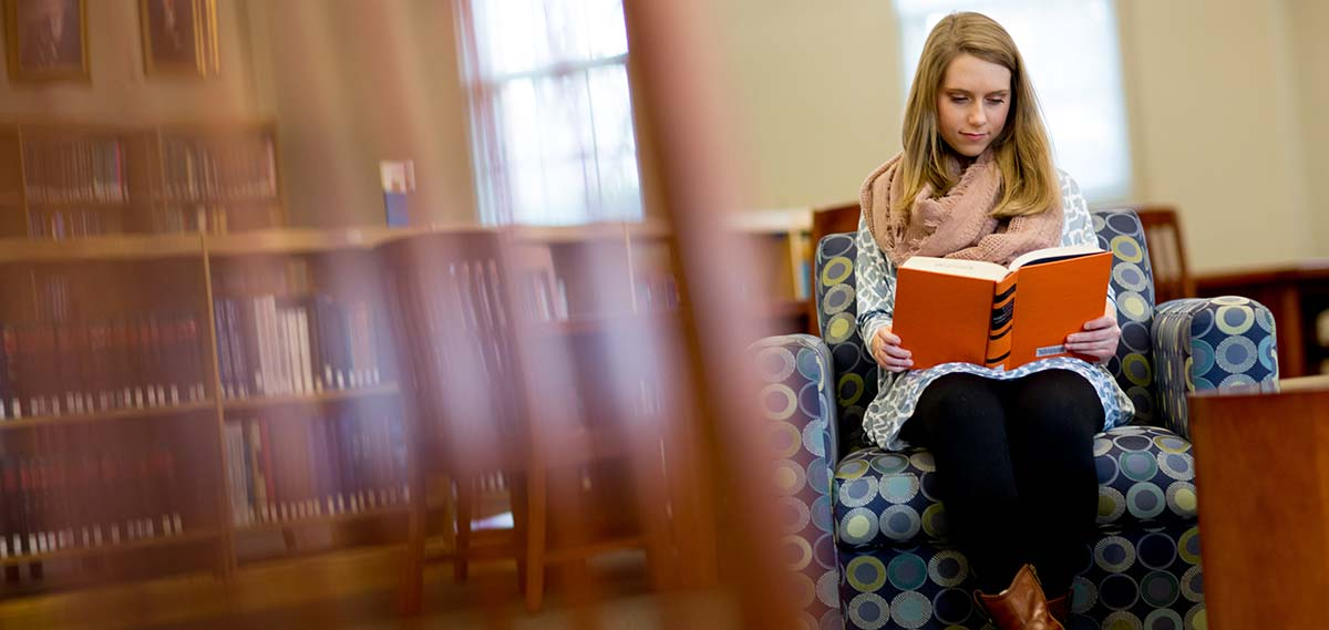 Female student sits on an armchair reading a book in the Leland Speed Library on Mississippi College's campus.